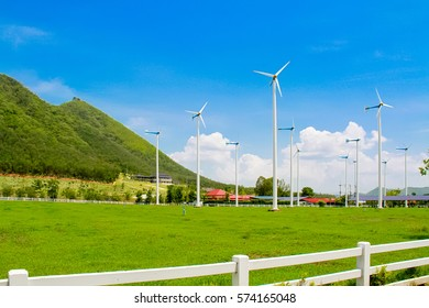 eco power : wind turbine generating electricity clean energy on green grass with mountain and cloud on blue sky background