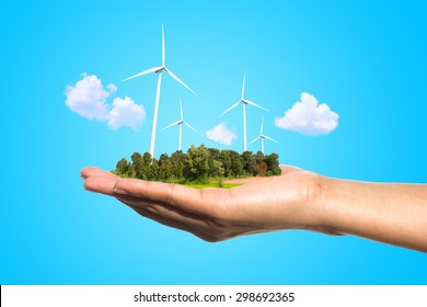 Eco power, wind turbines in the hand on blue background