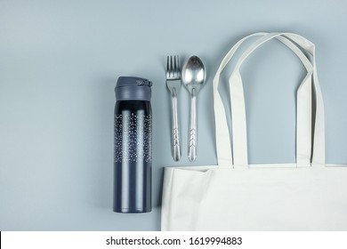 Eco Shopping bag, Stainless Steel spoon and fork, water bottle on gray background. Environmental Protection, Zero waste, Reusable, Say No Plastic, World Environment day and Earth day concept