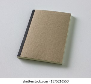 Eco sketchbook with front brown recycle paper and black tape spine, on isolated white texture background.