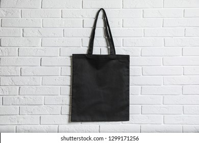 Eco tote bag hanging on white brick wall. Space for design