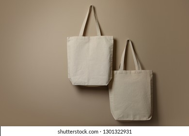 Eco tote bags hanging on color wall. Space for design
