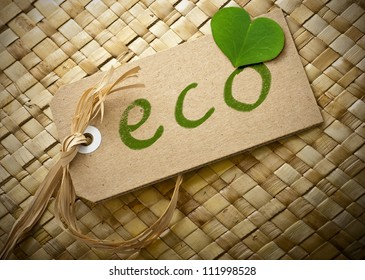 eco word written onto a cardboard label, green clover leaf, brown background