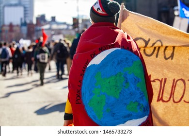 Eco-activists marching in the city. An environmental demonstrator is viewed from behind, marching on a crowded street with during a demonstration against climate change