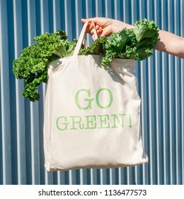 "Ecobag with inscription ""Go green!"" on the textured linen surface with green fresh kale"