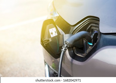 Eco-Friendly Alternative Energy Concept. Electric Car or EV Car Charging At Station With Power Cable Plugged In. Horizontal Image
