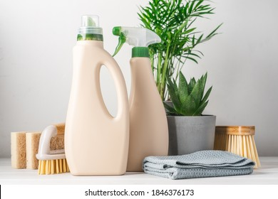 Eco-friendly bottled cleaning products. Reusable brushes and home green plants. Green life concept