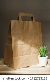 eco-friendly brown paper bag stands on a wooden shelf in the sun