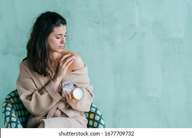 Öko-freundliches brunette hispanisches Weibchen, das Gesichts- oder Körpercreme oder Lotion in über grüner, minzfarbener Wand im modernen Interieur anbringt. Einflussfrau zeigt neues Produkt. Hautpflege, Wellness-Konzept.