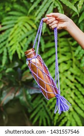 Eco-friendly copper bottle with knitted easy to carry strings shot over green leaves background