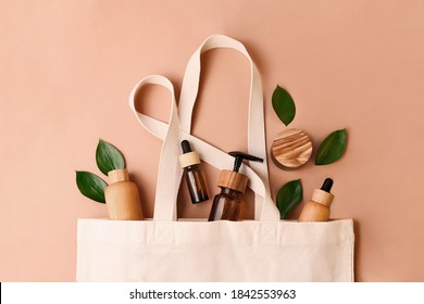 Eco-friendly cotton reusable bag with the different tubes and bottles from the natural wood and brown glass.Fresh natural leafs around.Concept of the organic,zero waste cosmetics.