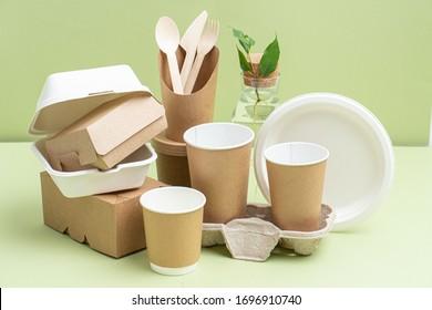 Öko-freundliche Einwegbambusbesteck, Papier- und Zuckerrohrbehälter für Lebensmittel und Getränke auf grünem Hintergrund. Seitenansicht auf Komposition. Verlegen Sie den Ast in Flasche.