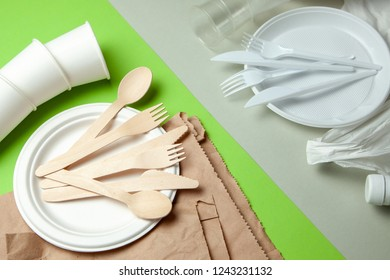 Eco-friendly disposable tableware made of bamboo wood and paper on a green background. Plastic harmful dishes and cutlery