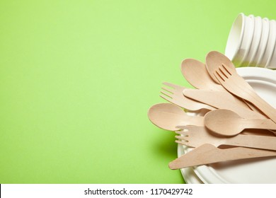 Eco-friendly disposable utensils made of bamboo wood and paper on a green background. Draped spoons, fork, knives, bamboo bowls with paper cups