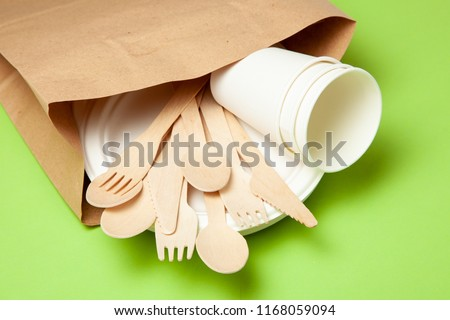Eco-friendly disposable utensils made of bamboo wood and paper on a green background. Draped spoons, fork, knives, bamboo bowls with paper cups and packet