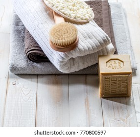 eco-friendly home spa still life with extra pure Marseilles olive oil solid soap, body brush and pile of cotton towels for green friendly bath or traditional body care concept over  wood background