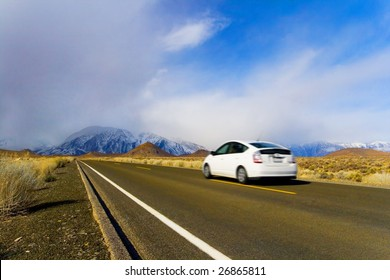 Eco-Friendly Hybrid Car in Motion, on Mountain Landscape