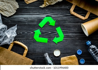 Eco-friendly life. Green paper recycling sign among waste paper, plastic, glass, polyethylene on grey wooden background top view