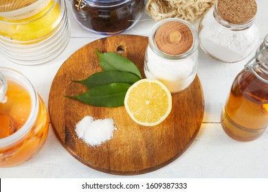 Eco-friendly natural cleaners: baking soda, soap, vinegar, salt, coffee, lemon and cloth with brushes on a wooden table