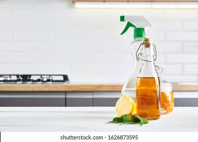 Eco-friendly natural cleaners: baking soda, soap, vinegar, salt, coffee, lemon and brush on wooden table. Kitchen background.