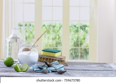 Eco-friendly natural cleaners baking soda, lemon and cloth on wooden table windows background,
