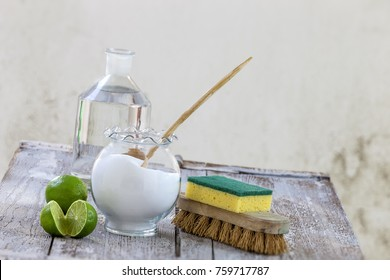 Eco-friendly natural cleaners baking soda, lemon and cloth on wooden background,