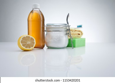 Eco-friendly natural cleaners. Vinegar, baking soda, and lemon on white background. Homemade green cleaning with Copy space