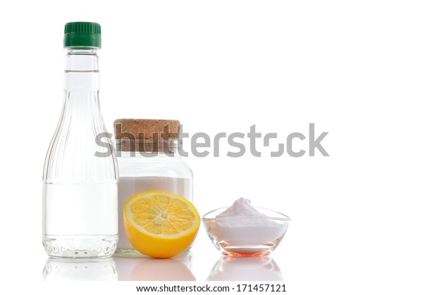 Eco-friendly natural cleaners. Vinegar, baking soda, salt and lemon on white background. Homemade green cleaning. Copy space.