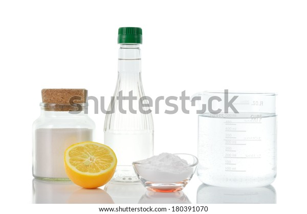 Eco-friendly natural cleaners. Vinegar, baking soda, salt, lemon and water in measuring cup on white background. Homemade green cleaning.