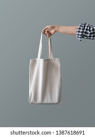 Eco-friendly product Zero waste concept A girl is holding a white blank canvas tote bag against a gray wall background