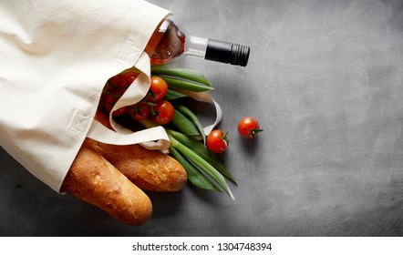 Eco-friendly reusable textile bag with groceries and wine spilling out onto a slate background with copy space