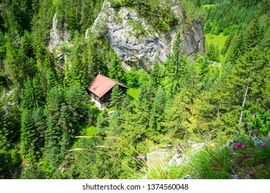 """Ecolog mountain hut as seen from high above on the """"Astragalus"""" via ferrata route, a popular sport attraction in Bicaz Gorge (Cheile Bicazului), Romania, on a bright, sunny day."""