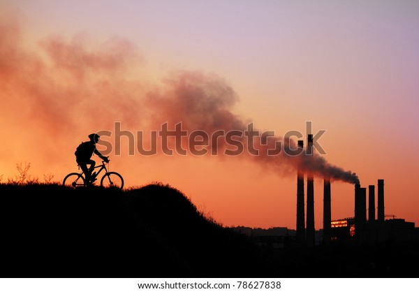 ecologic concept: silhouette of cyclist on factory pipes background