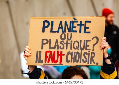 Ecological activists march for climate. A close up view of a French sign, saying plastic or planet, you have to choose as environmental protestors march on a street in Montreal, Canada.