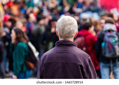 Ecological activists unite for climate. An older man is viewed from the rear with grey hair, contemplating a crowd of environmentalists marching in the city, people seen blurry in the background
