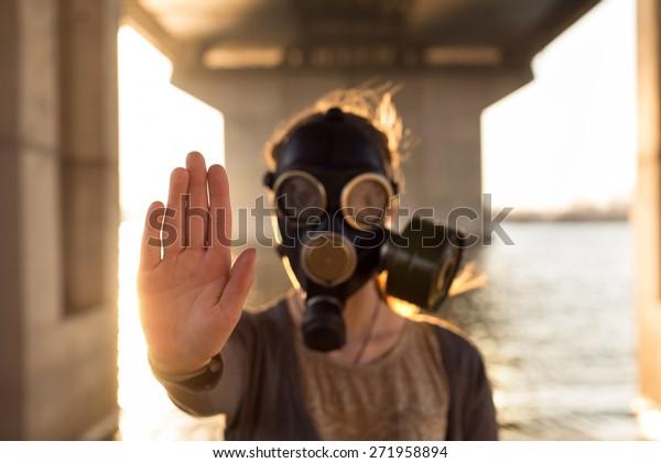 Concepto ecológico de contaminación del aire. Mujer enmascarada de gas cerca del agua mostrando gesto de parada