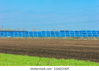 Ecological concept. Bioenergy and solar panels are amongst rural land in the green and plowed field
