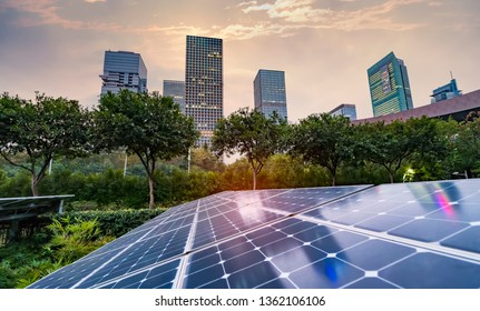 Ecological energy renewable solar panel plant with urban landscape landmarks in sunset