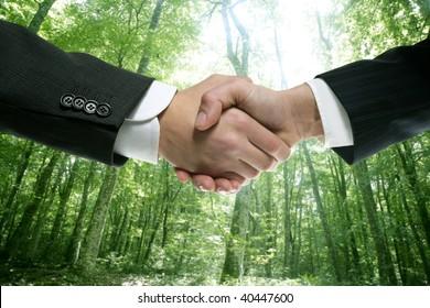 Ecological handshake businessman in a forest green background [Photo Illustration]