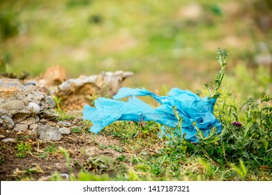Ecological pollution of nature. Plastic bag tangled in plants against the backdrop of the mountains. Global environmental pollution. Recycling, clearing the land from plastic debris.