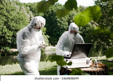 Ecological problem. Pollution. Examine soil. Scientist in protective mask and suit taking water samples from river. Chemist makes an analysis of the environment for radiation. Saving planet earth.