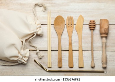 Ecological wooden cutlery, metal straws on wooden background and eco bags on wooden background. Top view. Concept zero waste.