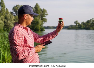 ecologist on river bank examines container with green algae and holds tablet