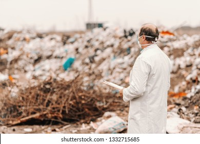 Ecologist in white uniform and mask on face holding clipboard, evaluating damage and looking at landfill. Backs turned.