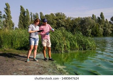 ecologists on river bank examine sample of green algae and enter info on tablet