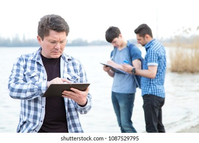 Ecologists are studying the pollution of the reservoir. Man is working on a digital tablet. Employee team of an environ mentalist on the background of a working group of men.