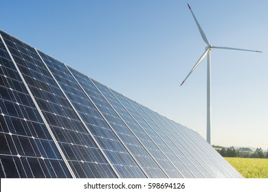 Ecology background with rapeseed field wind mill solar panel and electricity pole infrastructure - Renewable energies background