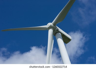 Ecology concept: Blue sky, white clouds and wind turbine. Wind generator for electricity, alternative energy source. Windmill for electric power production.