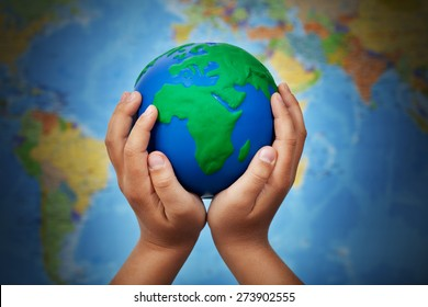 Ecology concept with earth globe in child hands against blurry world map