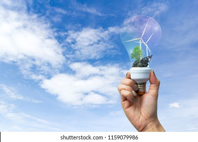 Ecology concept hand building electrical energy clean wind turbine and solar cell the future in light bulb